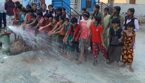 Well pump being tested and spraying fresh water in front of children